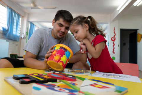 Xiomara, age 3, draws pictures with her father, David Fretes Paniagua, 27, in Paraguay.