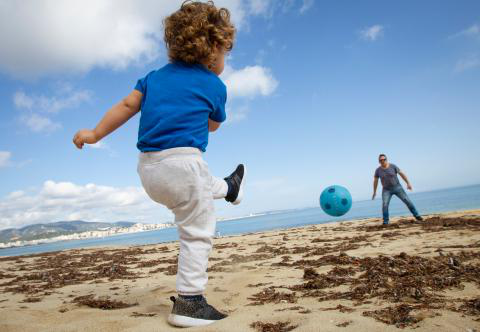 On 26 April 2020 in Palma de Mallorca, Spain, a child plays football with his father at Can Pere Antoni Beach during a national lockdown to prevent the spread of the COVID-19 disease.