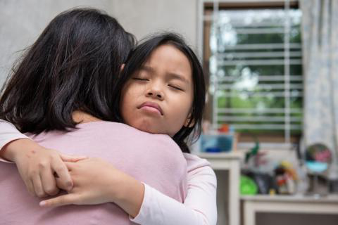 [NOTE: This is a stock image.] Mother and daughter hug tightly.