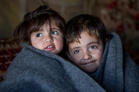 Two children nestle beside each other, wrapped in a thick grey blanket inside their family's tent in a refugee camp in Iraq.