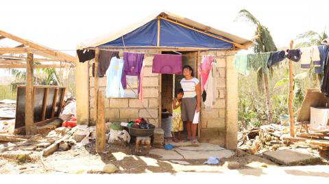 Philippines. A family stands outside their damaged home.