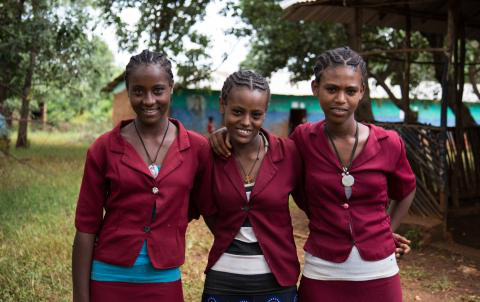 Three adolescent girls in Ethiopia stand shoulder to shoulder, smiling in their school uniforms.