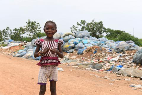 A girl playing in a l和fill, Côte D'Ivoire