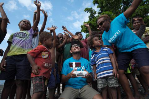 UNICEF representatives show children how drones will operate to deliver vaccines to their community.