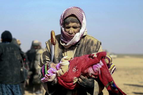 Syria. A man carries a small child in Baghoz village in Hajin district in eastern Syria.