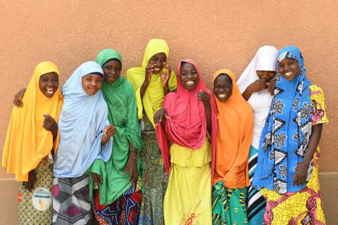Girls dressed colourfully in front of their school in Niger laugh and smile in 2019.