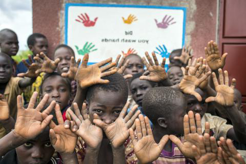 A group of children wave their hands, Uganda