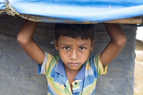 Bangladesh. A child stands under the plastic roof of a shelter in a refugee camp in Cox's Bazar.