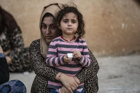 Syria. A woman stands with her child.