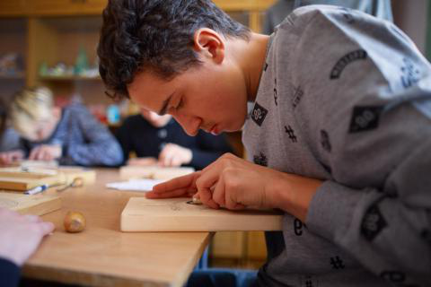 Volodymyr Charushyn, 16, at the wood carving lesson at his education complex for children with hearing disabilities in Ukraine He is a grantee of UPSHIFT Ukraine, an innovative programme aimed at developing entrepreneurship skills among adolescents 和 youth as agents of social change.