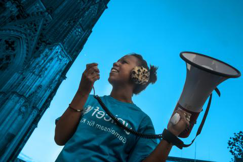 A girl in a blue UNICEF tee 和 holding a megaphone