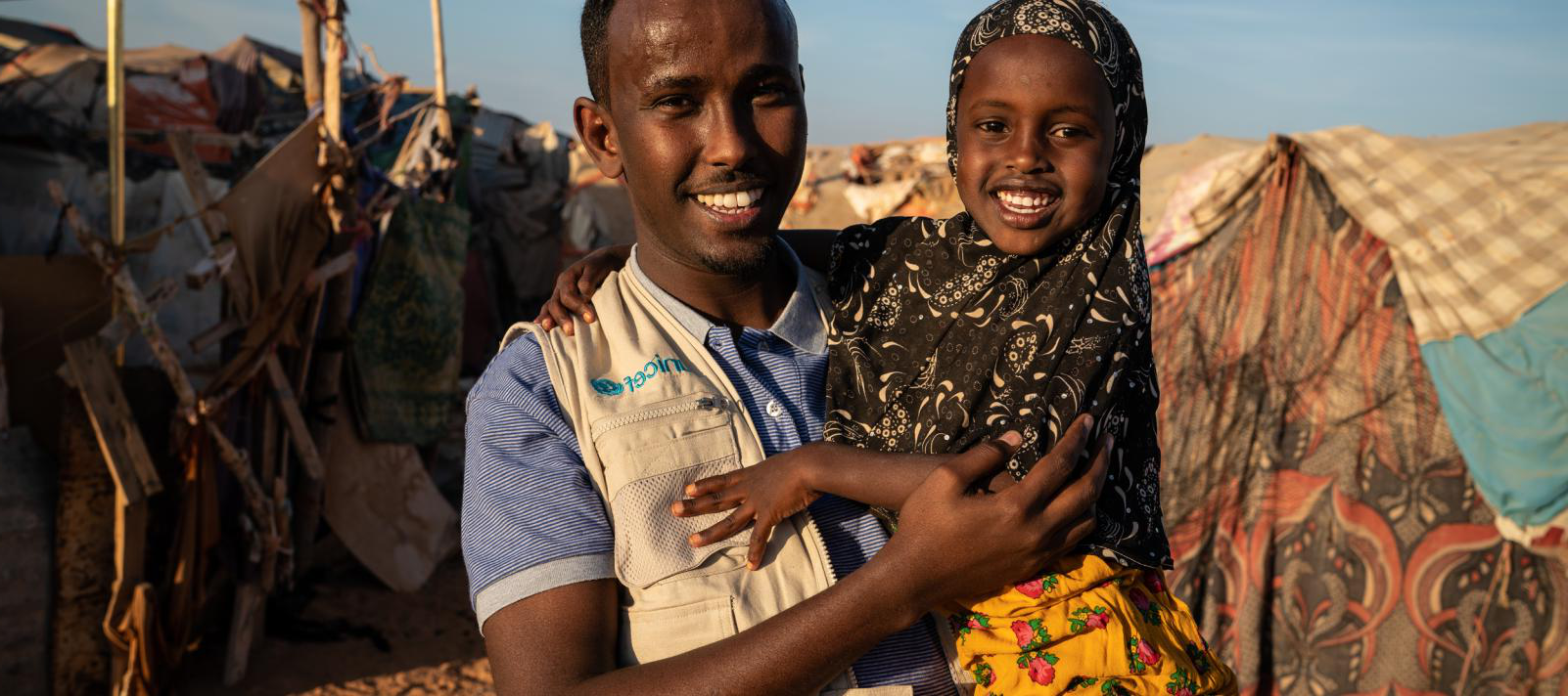 On 10 December 2018 in Somalia, UNICEF Child Protection Officer Ahmed Osman Adam speaks with a girl who lives in an IDP camp in Garowe.