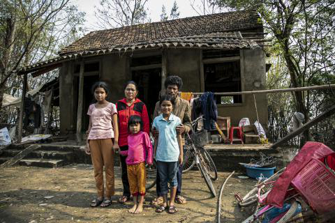 Nguyen Van Hat, 48 years old and his family stand in front of his house built and supported by the local authority some years ago. Mr. 哈t's family was reunited a few days after the terrible flood receded.